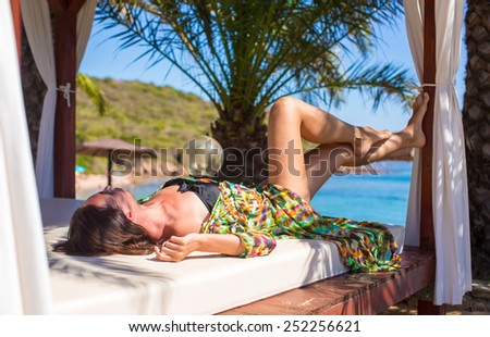 Young beautiful woman relaxing on beach bed during tropical vacation - stock photo