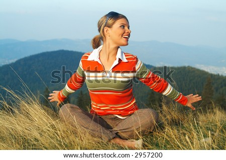 Young beautiful woman relaxing on meadow at mountain outdoors