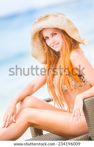 young beautiful woman relaxing on tropical sand beach, sky and sea background