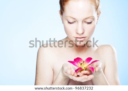 Young beautiful woman relaxing with lotus flower, professional beauty makeup