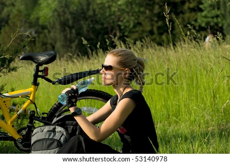 Young beautiful woman resting and drinking water after riding a bike - stock photo