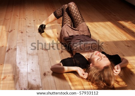 Young beautiful woman resting on the floor sunlit - stock photo