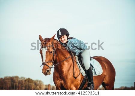 young beautiful woman rides a horse wearing a helmet. Horseback Riding. - stock photo
