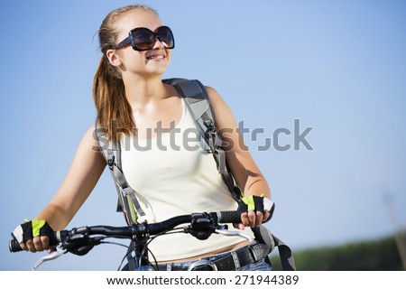 Young beautiful woman riding a bicycle in a park