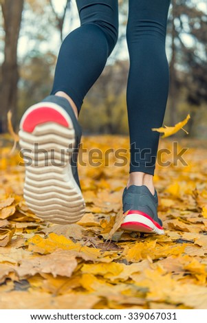 Young beautiful woman running in autumn park and listening to music with headphones. Legs close-up - stock photo