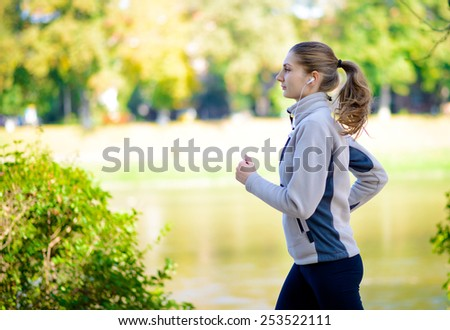 Young Beautiful Woman Running in the Autumn Park. Active Lifestyle - stock photo