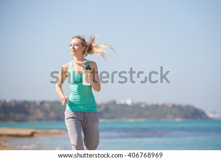 Young beautiful woman running on the beach at morning
