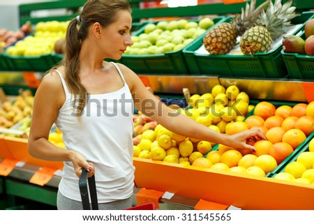 Young beautiful woman shopping in a supermarket in the department of fruit and vegetables - stock photo