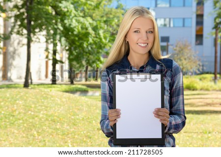 young beautiful woman showing clipboard with copyspace in autumn park - stock photo