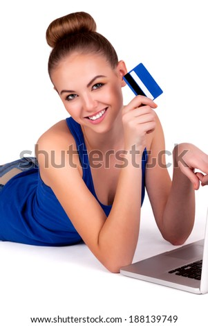 Young beautiful woman showing credit card having online shopping at computer