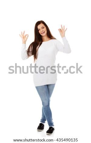 Young beautiful woman showing OK sign - stock photo