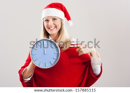 Young beautiful woman showing on the clock that  it`s midnight and a new year is here,Happy New Year!