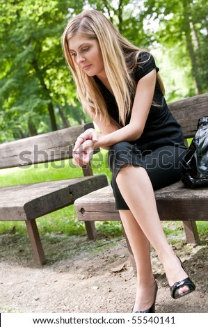 Young beautiful woman siting on bench in park in depression - stock photo