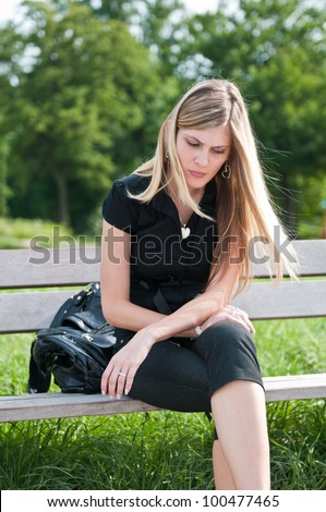 Young beautiful woman siting on bench in park in depression - looking down - stock photo