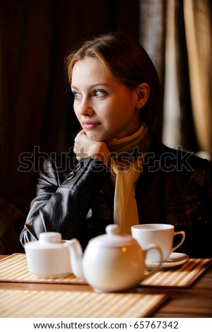 Young beautiful woman sits in cozy cafe, looks out of window and drinks hot tea from cup.