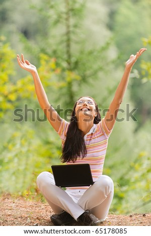 Young beautiful woman sits in pose of lotus with laptop and joyfully lifts hands upwards in summer green park.