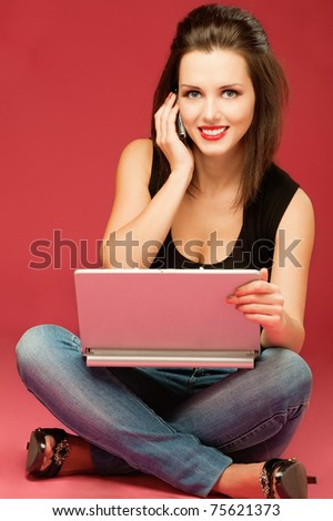 Young beautiful woman sits on floor with laptop and talks by mobile phone, on red background.