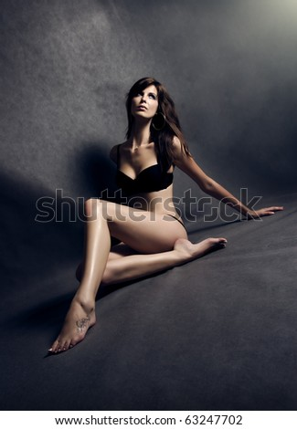 Young beautiful woman sitting at grey background