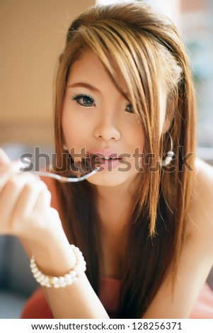 Young beautiful woman sitting in cafe eating  chocolate cake. Focus at the eyes. - stock photo
