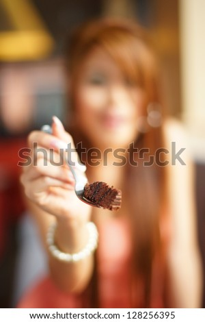 Young beautiful woman sitting in cafe eating  chocolate cake. Focus on cake. - stock photo