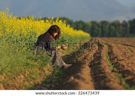 Young beautiful woman sitting near a yellow flowered field - stock photo
