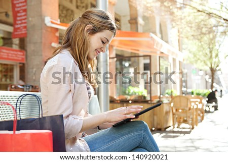 Young beautiful woman sitting on a bench in a city center with her shopping bags during a sunny day, using a digital tablet pad near a coffee store bar, smiling. - stock photo