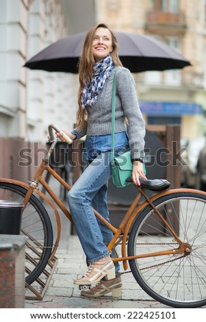 Young beautiful woman sitting on a bike in the street happy smiling - stock photo