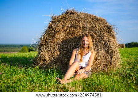 young beautiful woman sitting on a green meadow against a haystack - stock photo