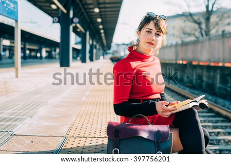 Young beautiful woman sitting on a platform in a train station reading a book, looking in camera - student, commuter, reading concept - stock photo