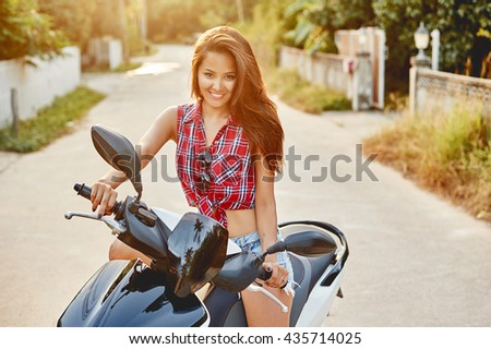 Young beautiful woman sitting on a scooter  - stock photo