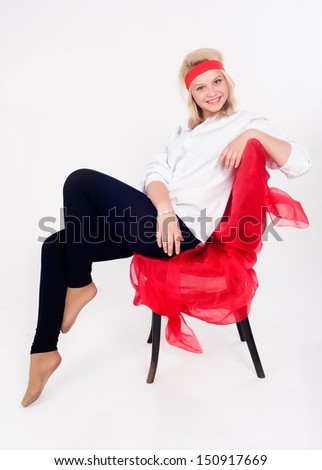 Young beautiful woman sitting on chair at white bsckground - stock photo