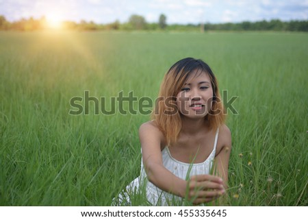young beautiful woman sitting on grassland enjoy nature and fresh air happy. - stock photo