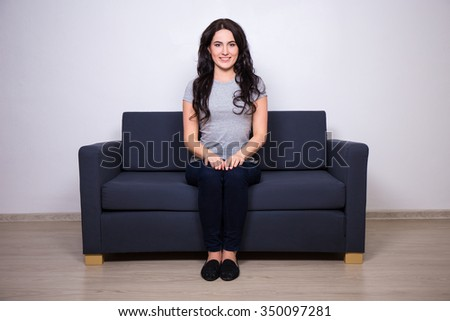young beautiful woman sitting on modern sofa in living room - stock photo
