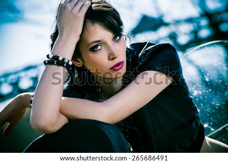 young beautiful woman sitting on motorbike,  outdoor at river port - stock photo