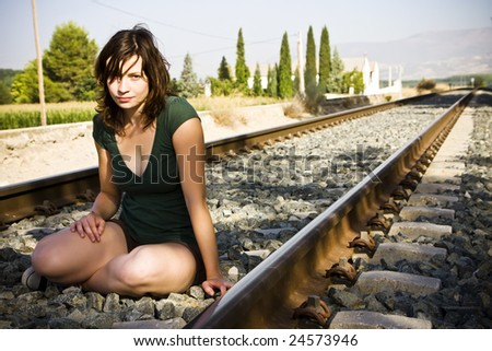Young beautiful woman sitting on railtrack - stock photo