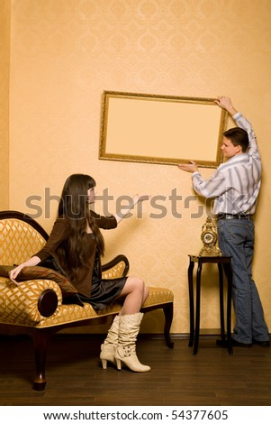 young beautiful woman sitting on sofa in room and smiling man hang up on wall picture in frame, looking against each other - stock photo