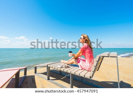 Young beautiful woman sitting on the beach chair with  shoes and drink coffee.
