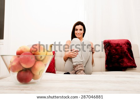 Young beautiful woman sitting on the couch wearing worn-out socks - stock photo