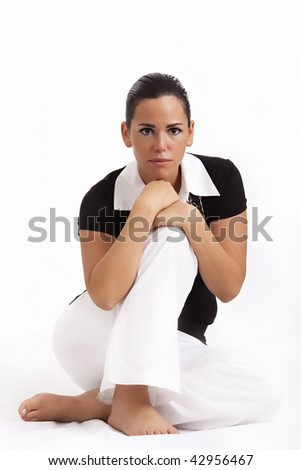 Young beautiful woman sitting on the floor, white background - stock photo