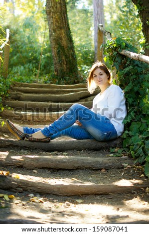 Young beautiful woman sitting on the rural stairs in the forest. Autumn time