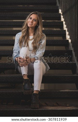 Young beautiful woman sitting on the stairs at the city. Urban shot. - stock photo