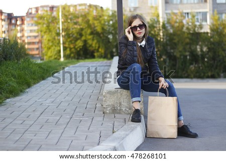 Young beautiful woman sitting with paper shopping bag.
