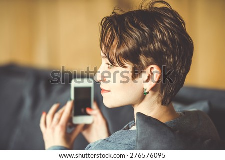 Young beautiful woman sitting with smart phone. Toned picture - stock photo