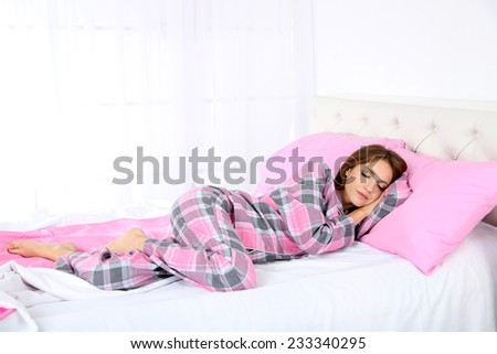 Young beautiful woman sleeping in bed close-up - stock photo