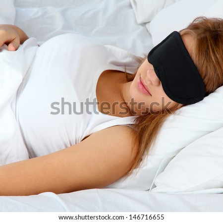 young beautiful woman sleeping in bed with eye mask - stock photo