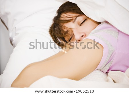Young beautiful woman sleeping in white sheet.