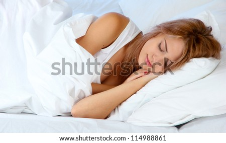 young beautiful woman sleeping on bed on blue background - stock photo