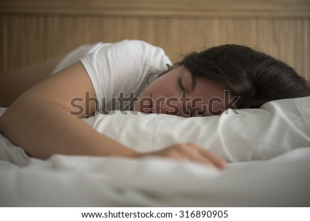 young beautiful woman sleeping on the bed - stock photo