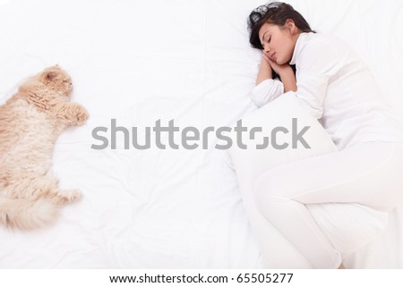 Young beautiful woman sleeping on the bed with her cat - stock photo