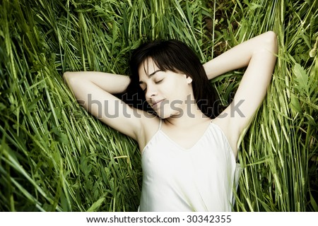 Young beautiful woman sleeping over the grass - stock photo